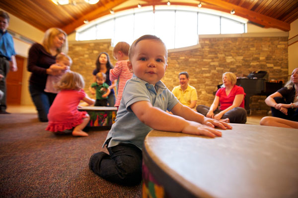 Toddler boy with gathering drum in Music Together class